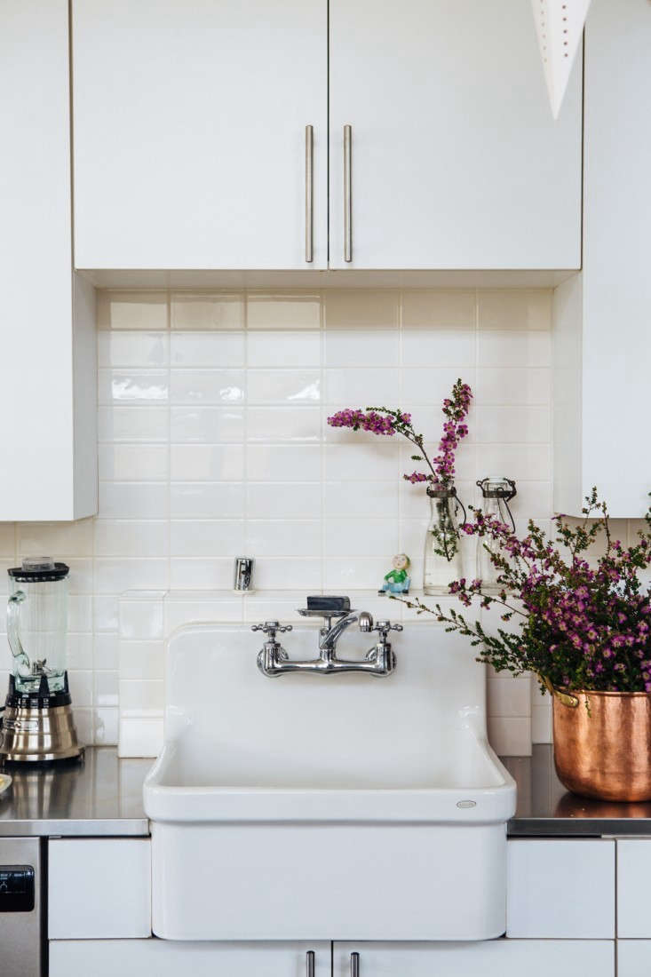 Modern white cabinets stand in contrast with the black Shaker-style kitchen island. Photograph by Laure Joliet from Joan McNamara's Industrial Chic Loft in LA.