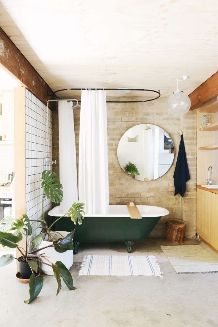 A salvaged dark green clawfoot tub takes center stage in an apartment bath. See more inOutbuilding of the Week: Garage Turned Studio Apartment. Photograph by Lauren Bamford.