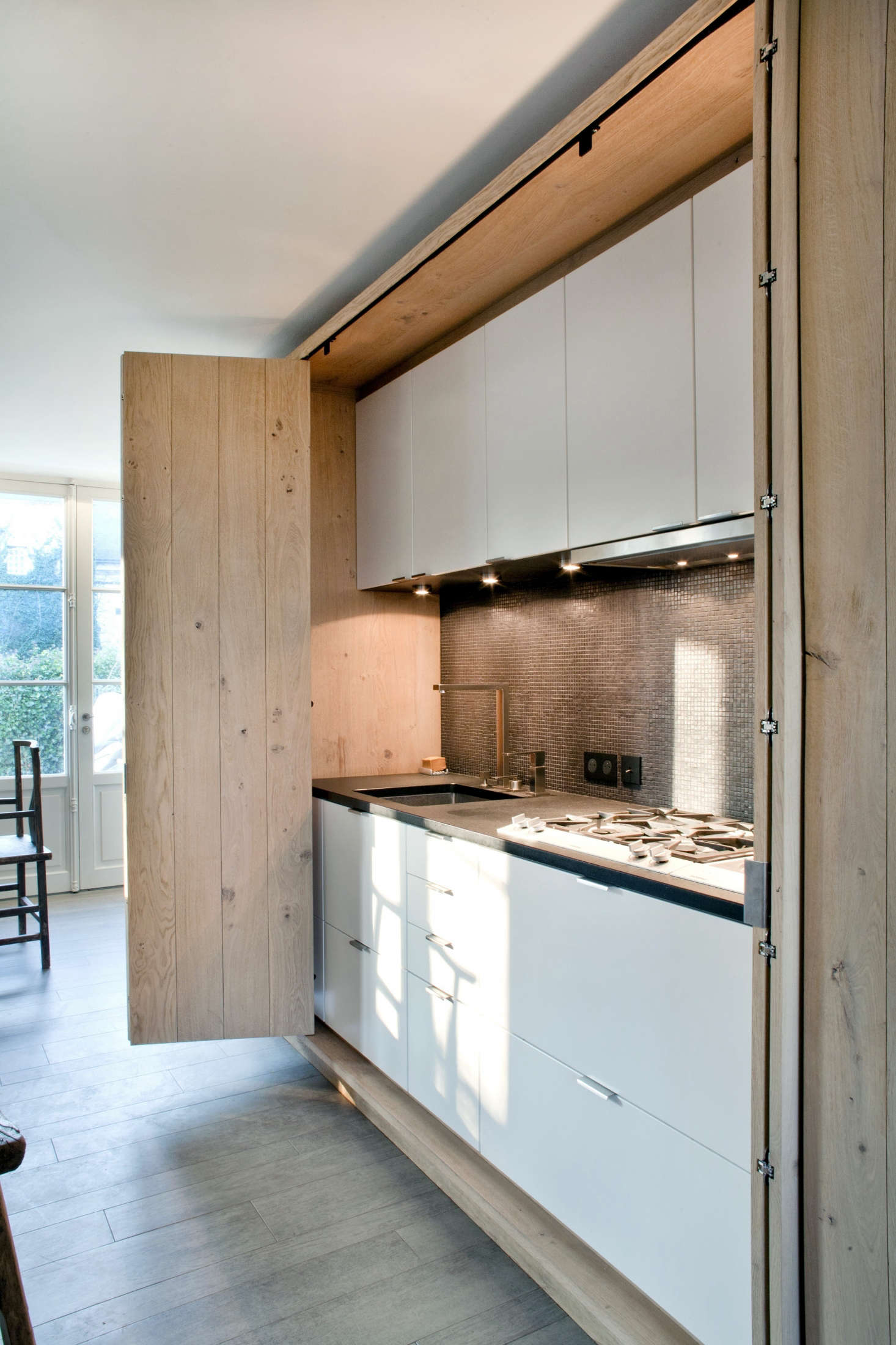 French architect Olivier Chabaud concealed an entire kitchen behind folding doors in this country house.