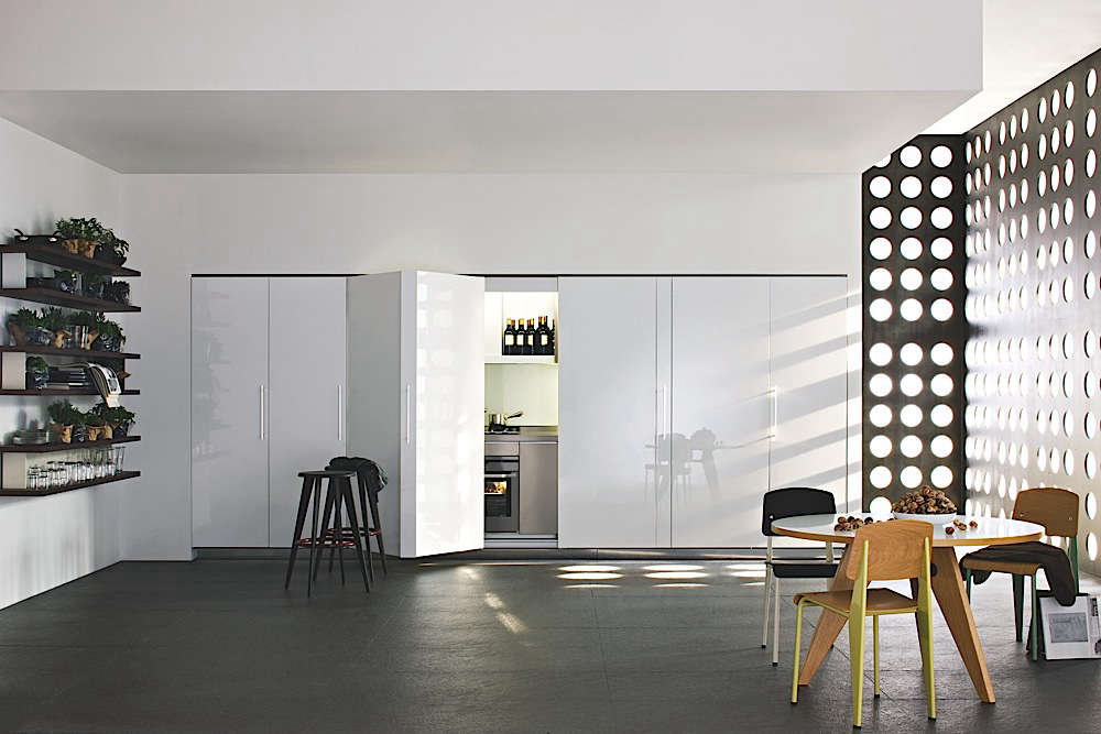 The Tivali Kitchen from Dada in Italy is tucked behind folding doors.
