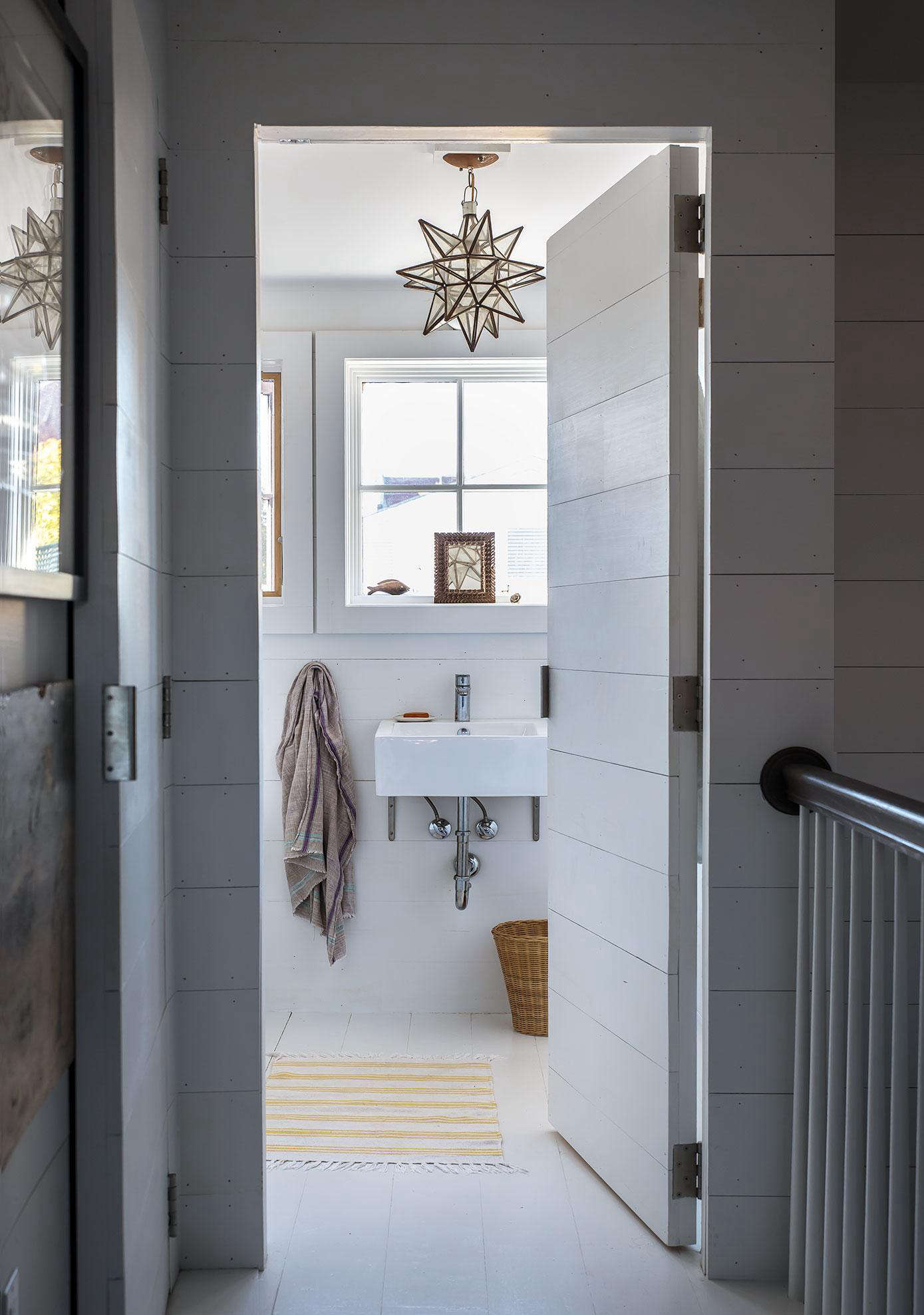 The bathroom and full upstairs studio are paneled with horizontal poplar Trim Boards from WindsorOne for a shiplap effect. Photograph by Justine Hand fromLiving Above the Shop: Ceramic Artist Paula Greif in Hudson, NY.