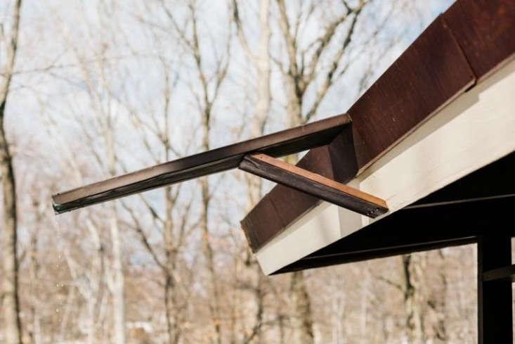 a rain spout protrudes from a copper trimmed roof atthe wood house: a midcent 17