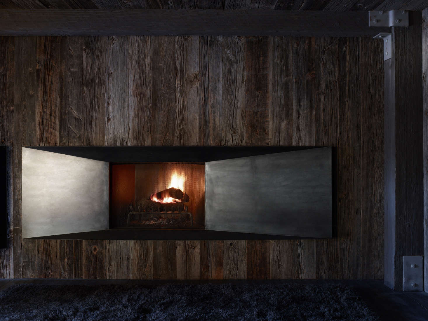 Raw steel doors close off the fireplace when it&#8