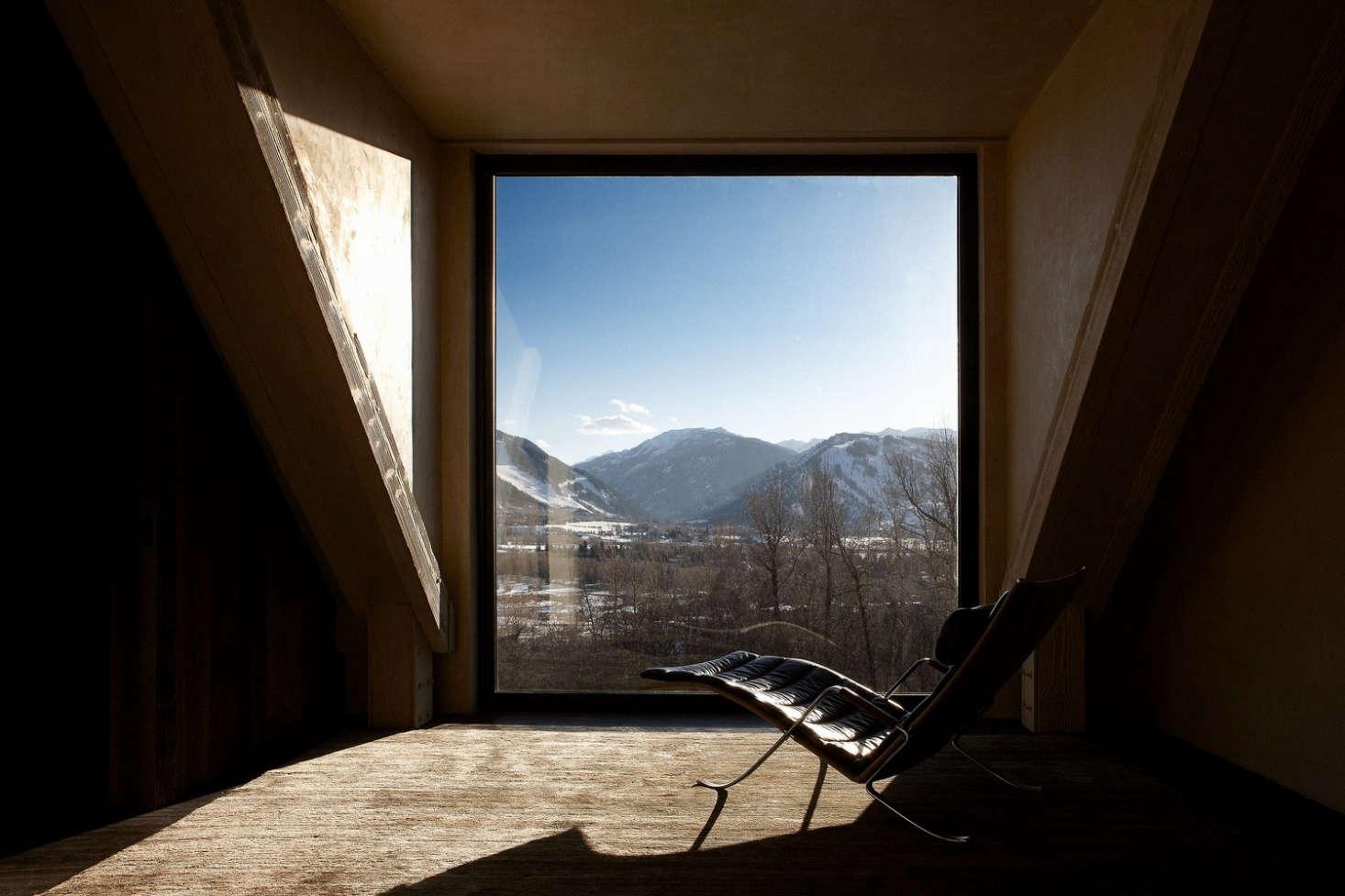 A large window overlooks the mountain range outside.
