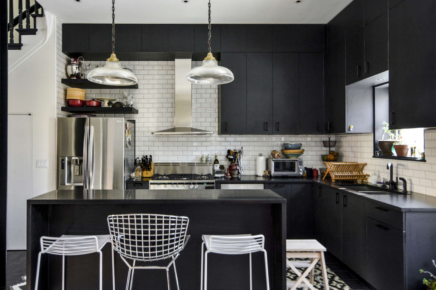 A Brooklyn kitchen has Ikea Sektion base cabinets fitted with custom doors ofChemetal Magnetic Chalkboard Laminate, EmtekBrass Trail Pulls, beveled subway tiles, and black honed granite countertops. For more, seeTwo Young Architects Tackle Their Own Brooklyn Townhouse.