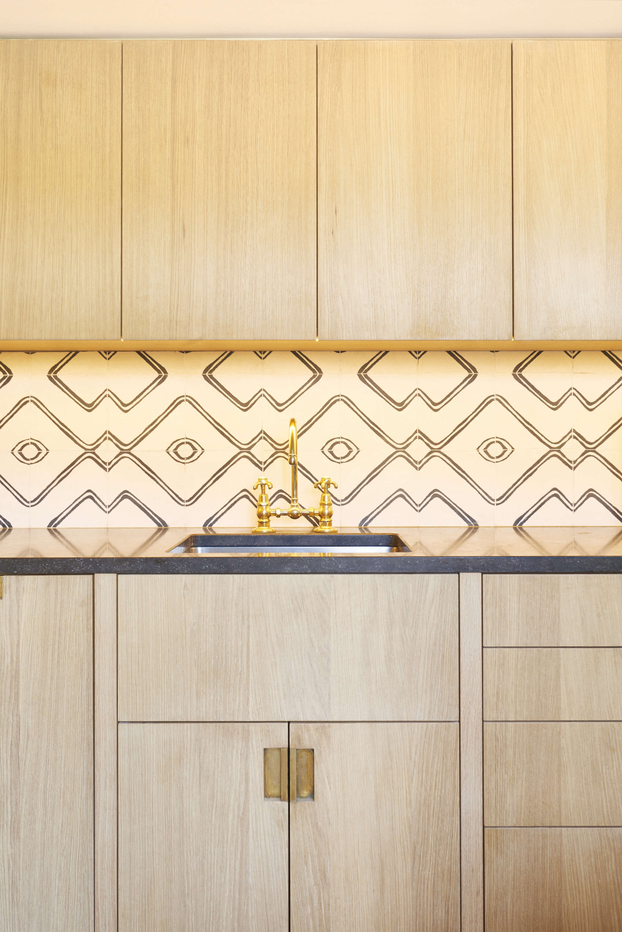 an unlacquered brass bridge kitchen faucet, paired with custom oak cabinets and 11