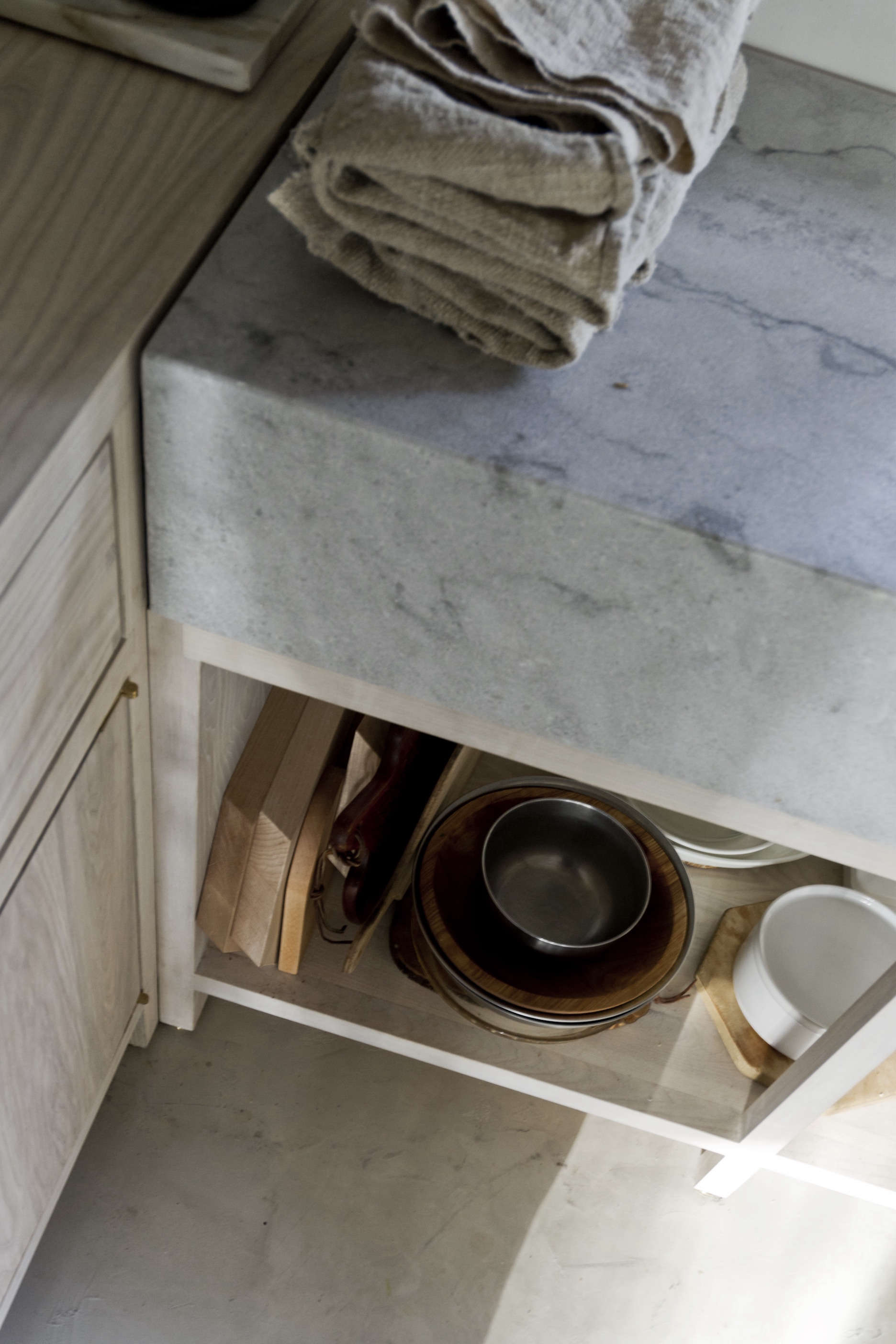 Cutting boards and pots and pans—all wood, metal, and white enamelware—are stored under the counter.David&#8
