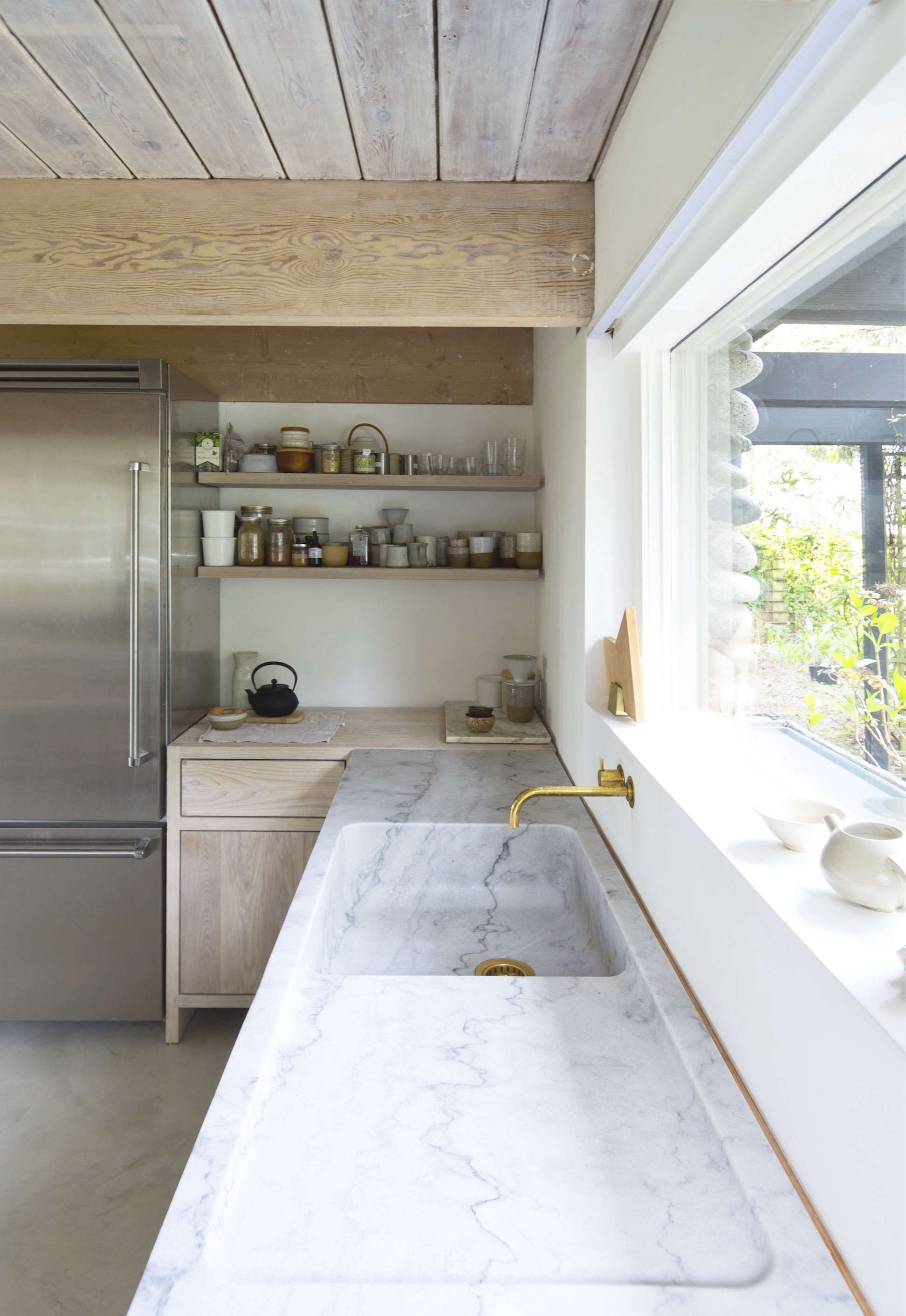 The counter stretches for eight feet (the woodenfill stripbetween sink and wall has since been painted white). Above the window, the work area is lit by a linear LED light manufactured by MP Lightingof Vancouver. The inset range hood, shown below, also has a light—and that&#8