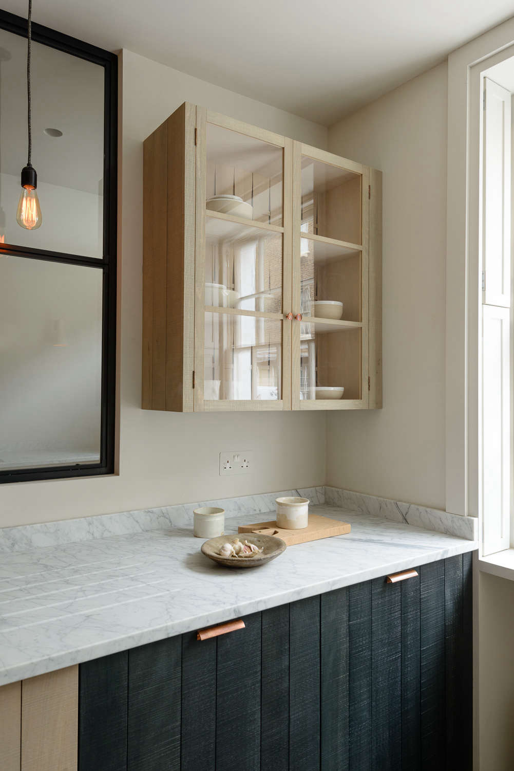 Glass-fronted wall cupboard in the Marylebone London Galley by Simon Cox for DeVol | Remodelista