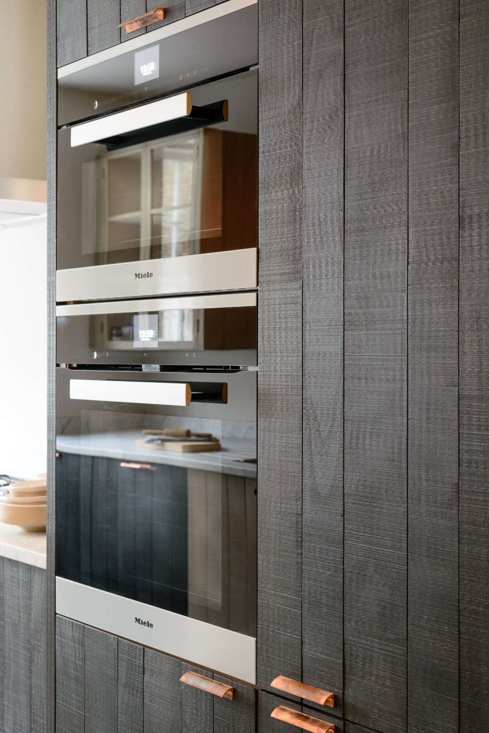 Black wood-paneling with wall oven in the Marylebone galley by DeVol | Remodelista
