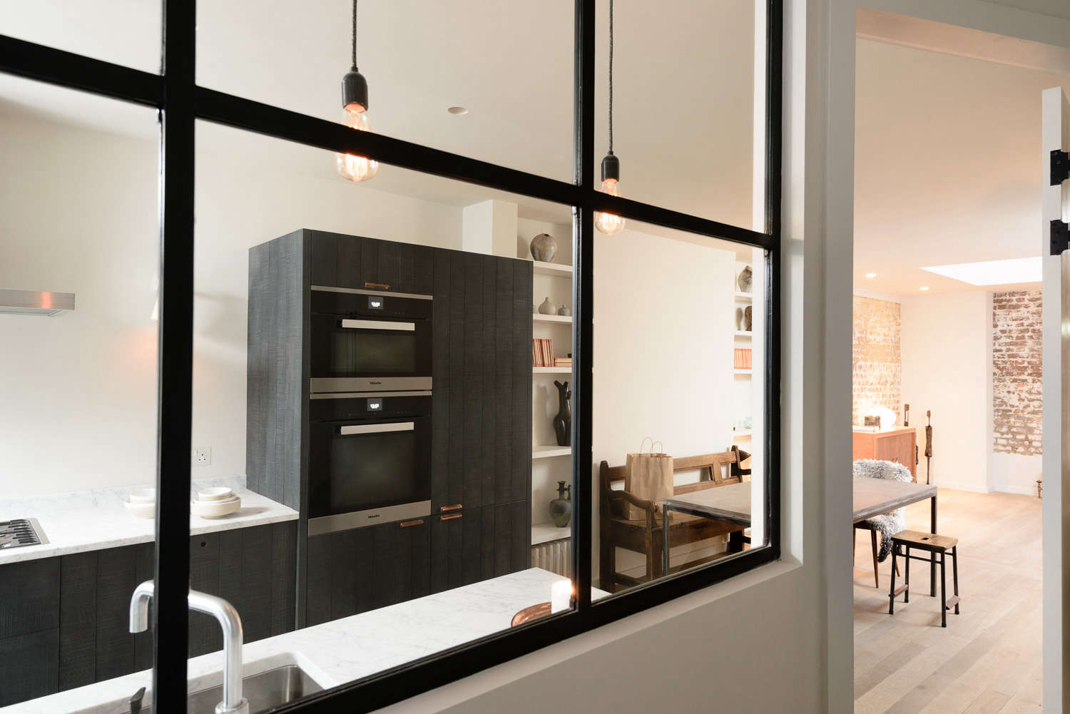 Black wood paneled cabinets and marble counters in the Marylebone kitchen by Simon Cox for DeVol | Remodelista