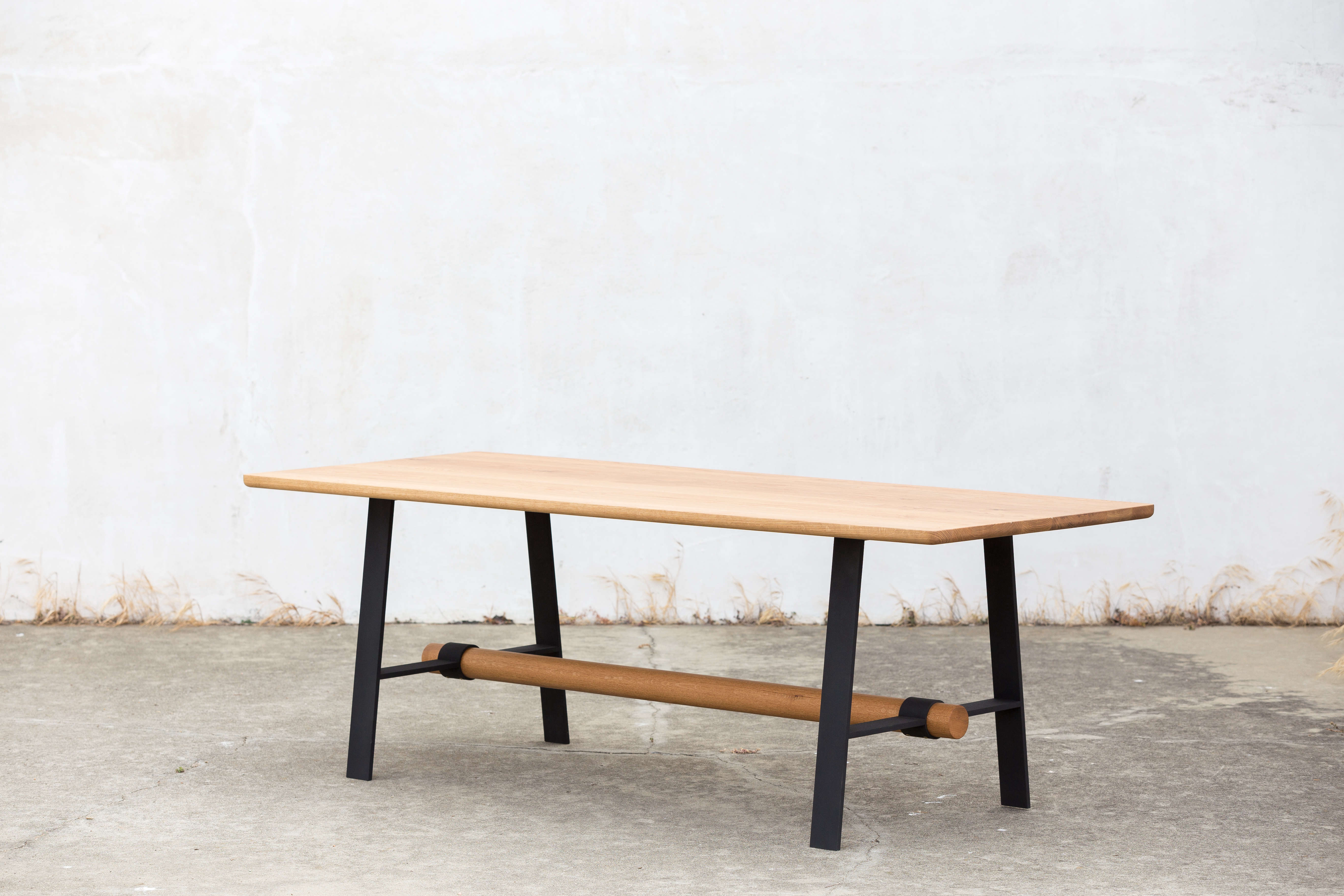 The Dowel Dining Table, shown in natural white oak and black steel legs, features a long dowel trestle that inspires the rest of Four/Quarter's work. Contact Four/Quarter for pricing and information.