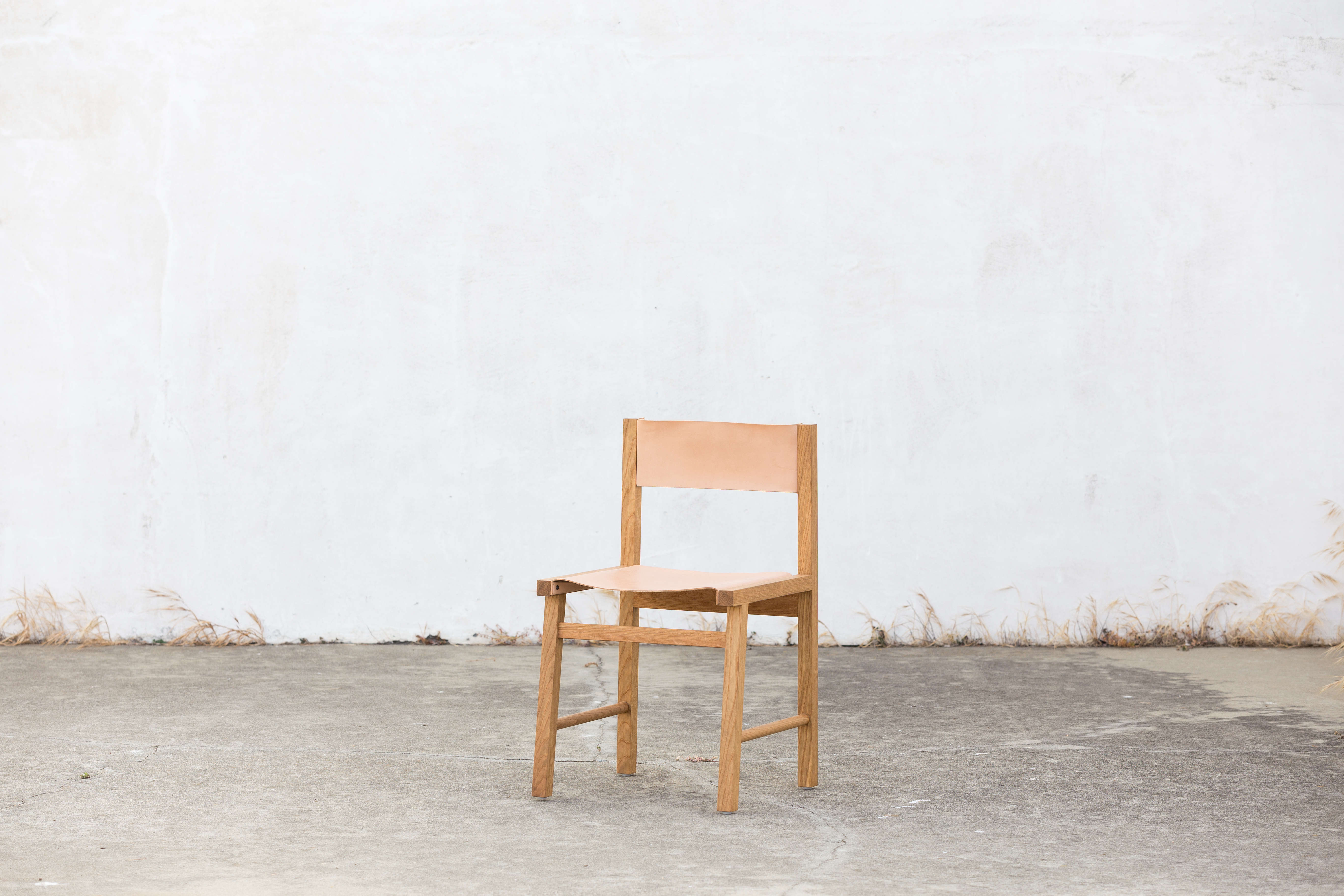 The Dowel Sling Chair in natural white oak with a vegetable tanned leather seat.