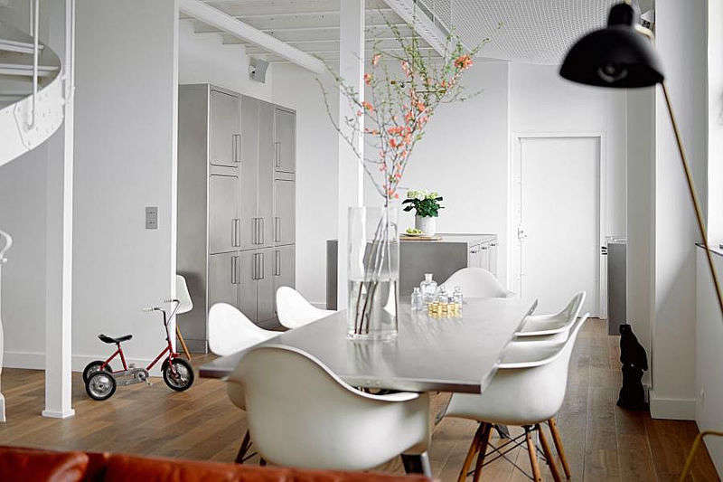 A Festen-supplied stainless steel table and white Eames Molded Plastic Dowel-Leg Armchairs create a graceful segue between kitchen and living area. The double helix stair, out of frame at left, is the perfect companion for the stainless equipment.