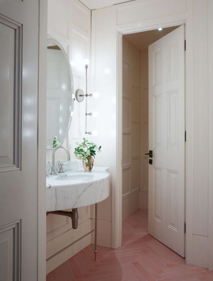 an otherwise white bathroom at spring restaurant in london gets a dose of pink  17