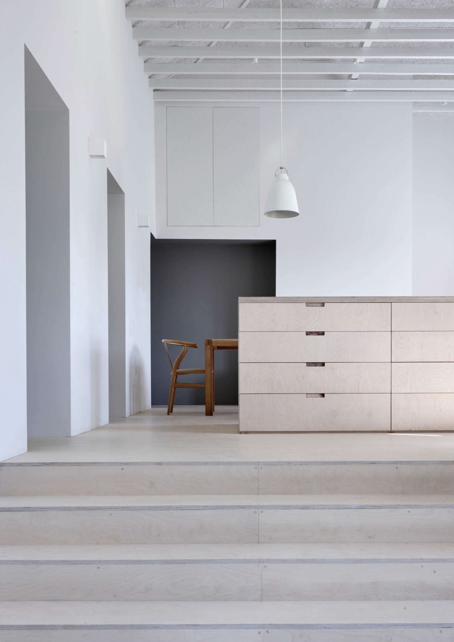 A Caravaggio P3 Pendant Light hangs over the central island, which like the steps, floor, and other cabinets are madeof birch plywood finished with a clear matte oil.