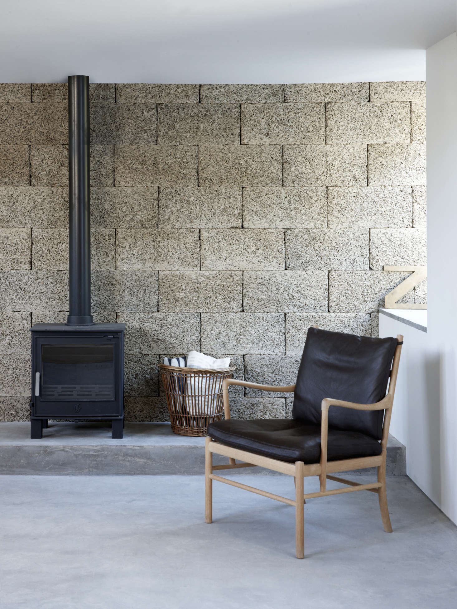 Textural wood wool blocks form the living room back wallandlend an intimacy to the space. (Also known as excelsior, these compressed strands of wood bonded with cement are traditionally used among other things as insulation.) The armchair is Ole Wanscher&#8