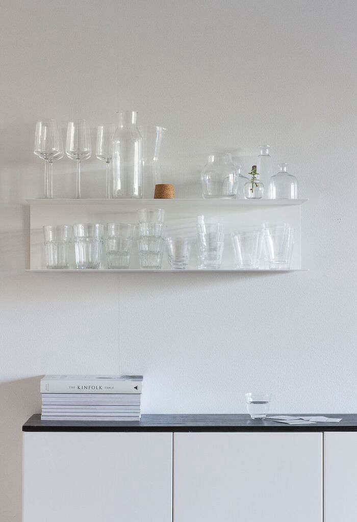ikea bent metal shelving holds glassware. the white paint used throughoutis b 15
