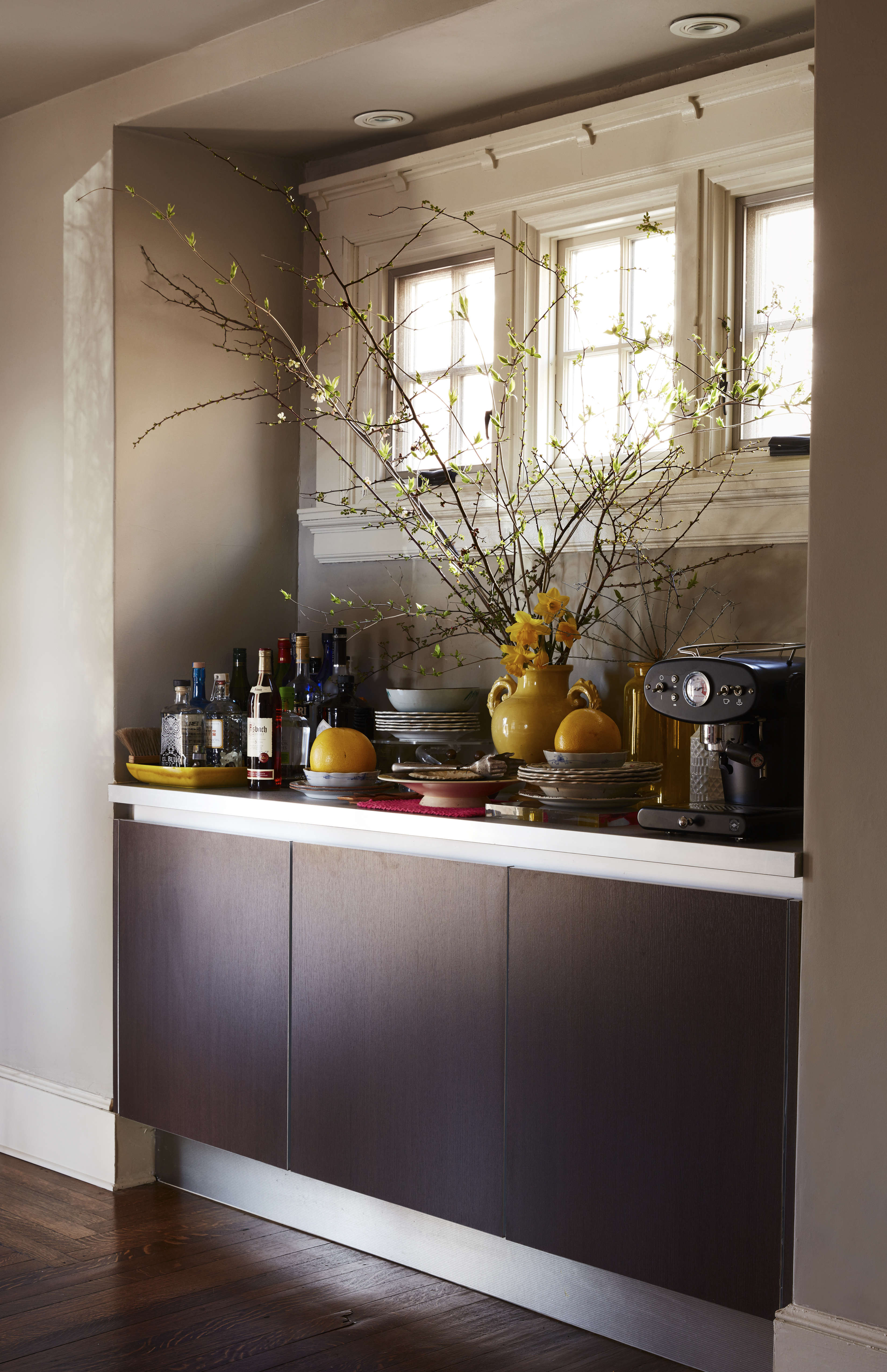 The dining room opens to the kitchen, so the couple linked the two by inserting a Poggenpohl sideboard and Ikea counter. Livia carried home the Illy coffeemaker from a trip to Italy—&#8