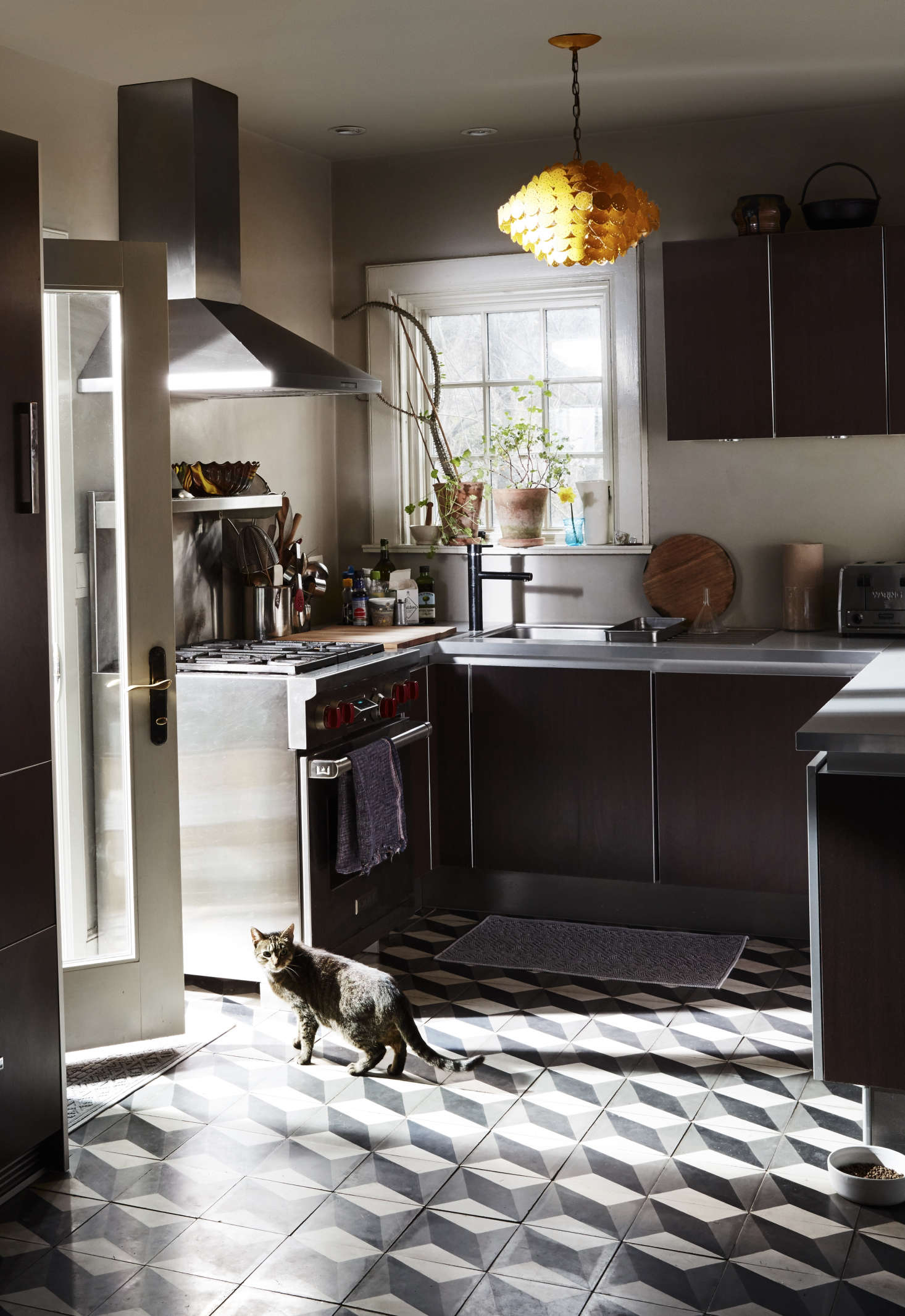 In the kitchen, the couple splurged on a hardware-free design in dark oak with aluminum framing from Poggenpohl&#8