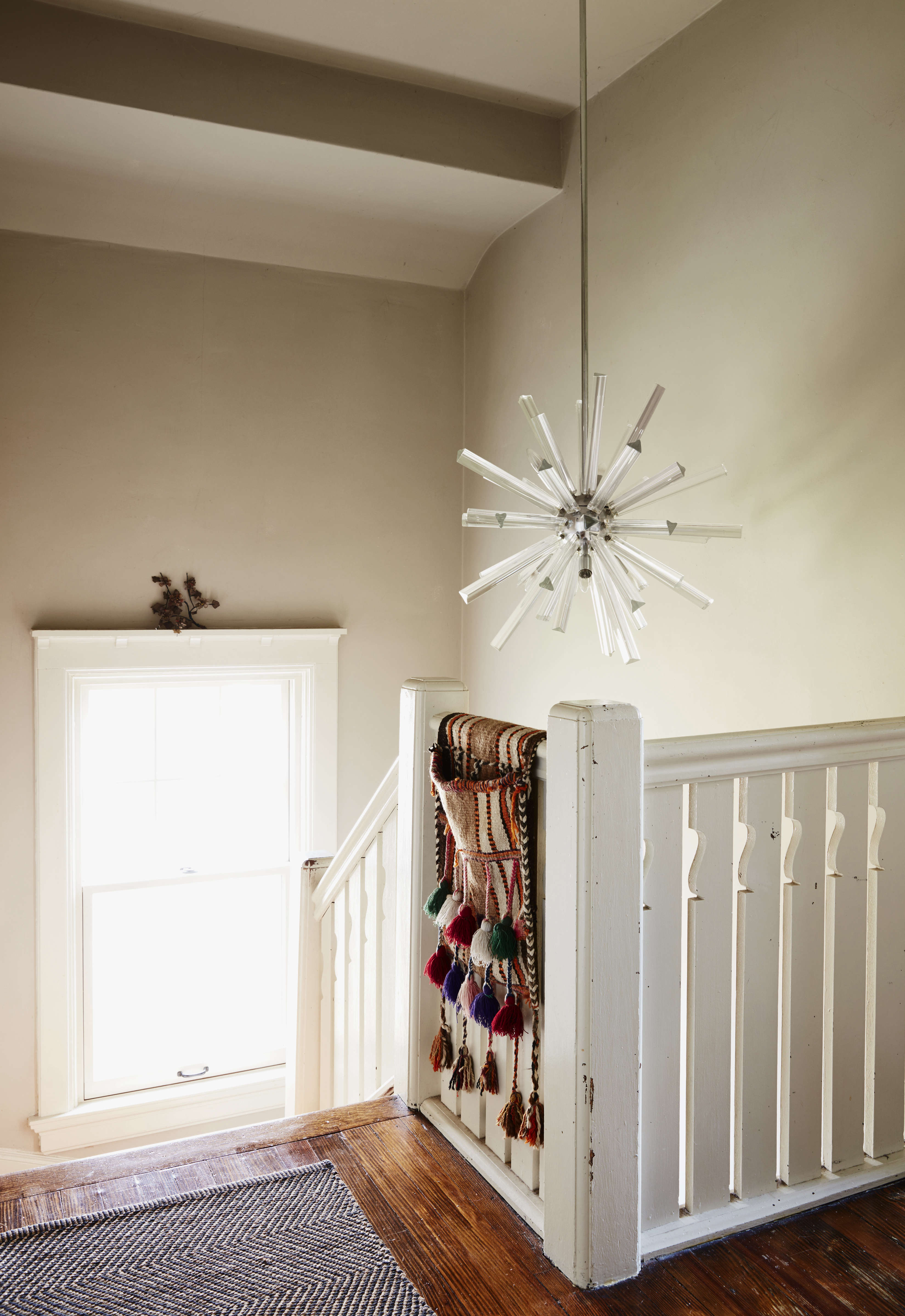 The upstairs landing is hung with a 60sMurano glass fixture that Danny got from a client who was getting rid of it. The tasseled saddlebag came fromNine Streets New York, one of Livia&#8