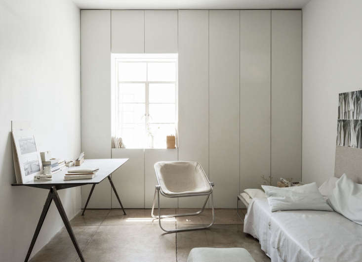Custom built-ins surround a window in the all-white Pasadena bedroom of designerMichaela Scherrer, creating plenty of concealed storage, plus a ledge for artful displays. See World's Tiniest Spa Bath: A Grecian-Inspired Guest Suite in LA for more; photograph byMatthew Williamsfor Remodelista.