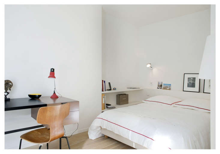 A ledge and bedside shelving take the place of tables in a small Paris bedroom designed by architect Philippe Harden. The midcentury desk is by Pierre Paulin.