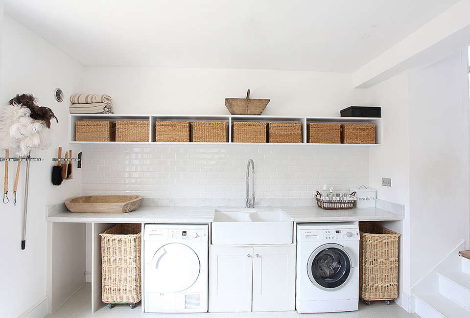The washer and dryer are each flanked by a niche for a rolling hamper in Steal This Look: A Well-Equipped Laundry Room in Somerset.