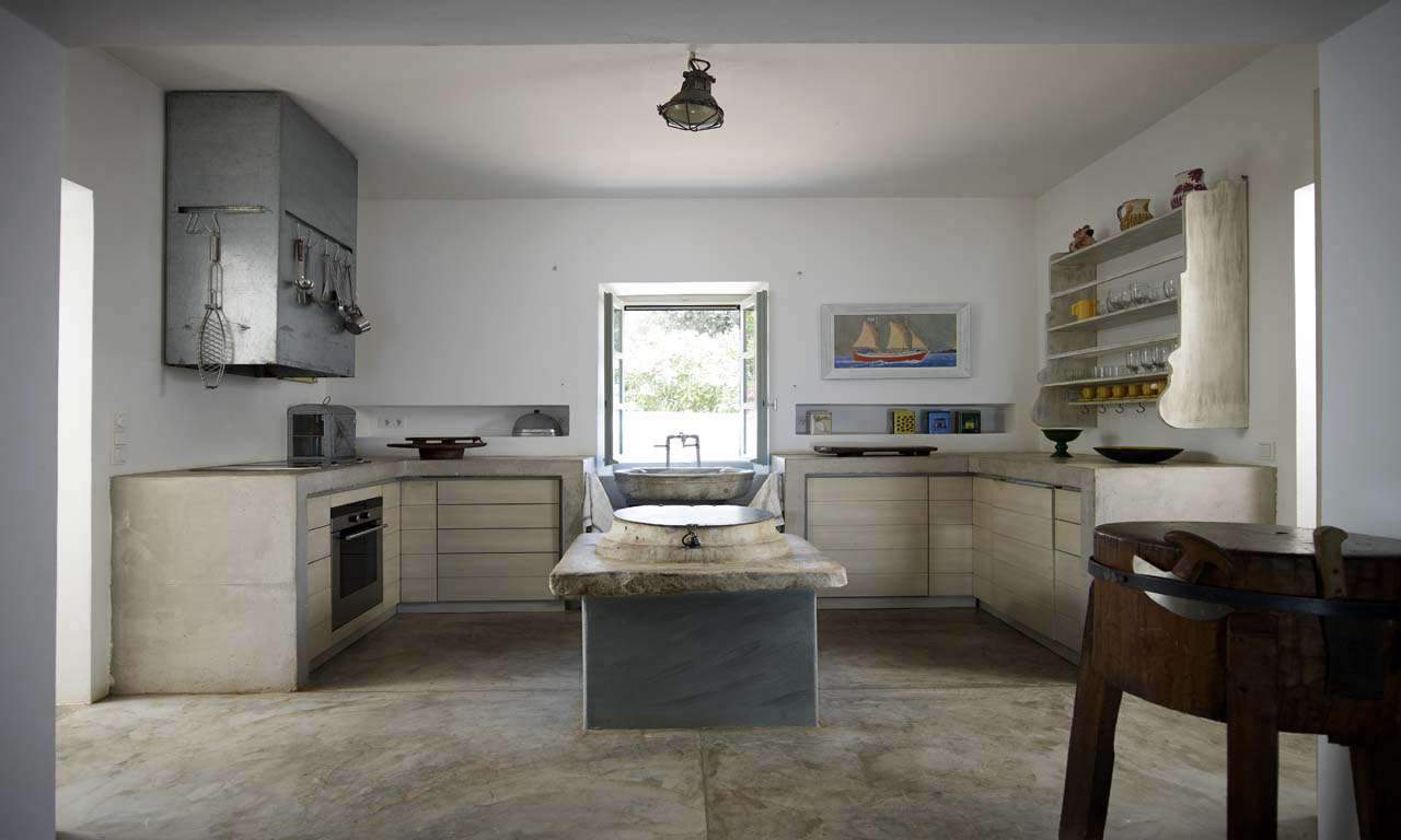 """""""I tried to make the entire kitchen in one finish: The poured concrete on the floor climbs and creates the worktops,"""" says architect Theodore Zoumboulakis of the kitchen in his house on the Greek isle of Hydra. """"This finish is very simple, the simplest it could get, and seemed appropriate forthe arid rocky surroundings and beach."""" Photograph courtesy of Zoumboulakis Architects."""