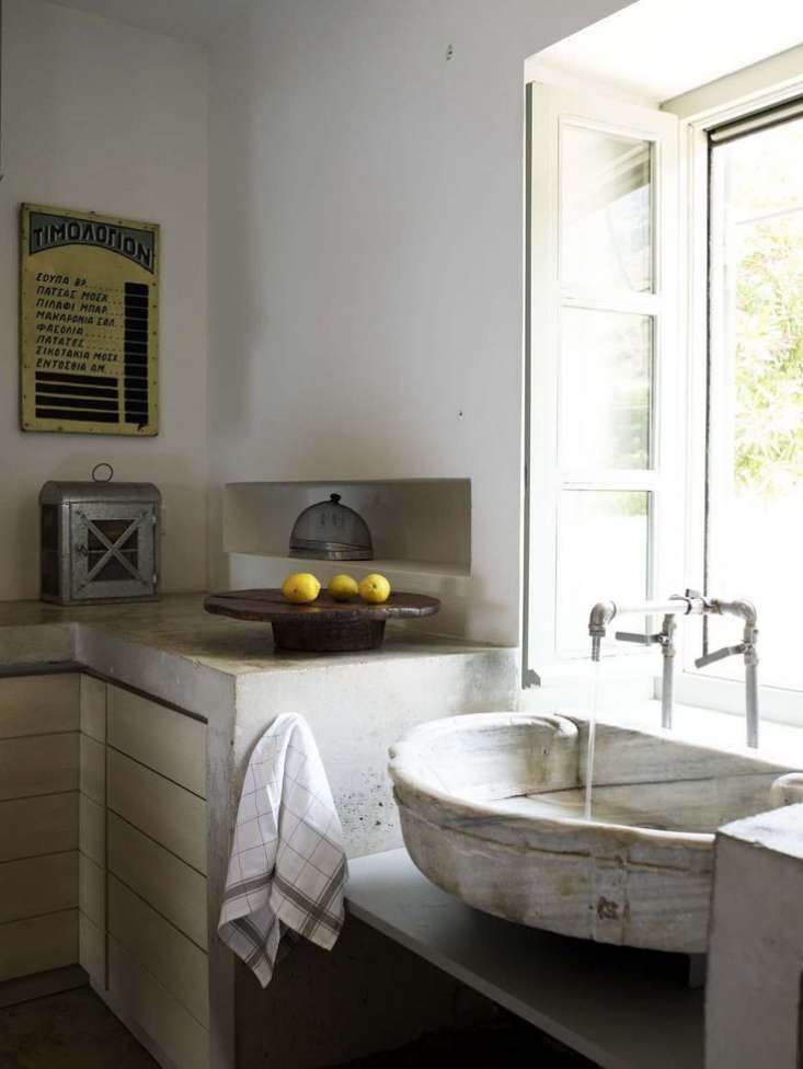 An antique marble fountain basin serves as the kitchen sink. And the faucet? &#8