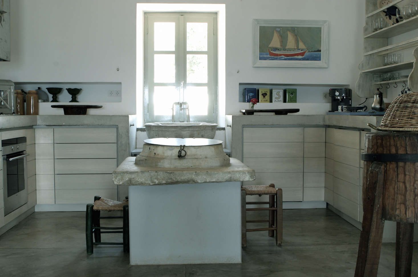Also from the family collections, a marble piece from an old well serves as the top of the pale blue concrete kitchen island. Photograph byCostas Picadas, courtesy ofZoumboulakis Architects.