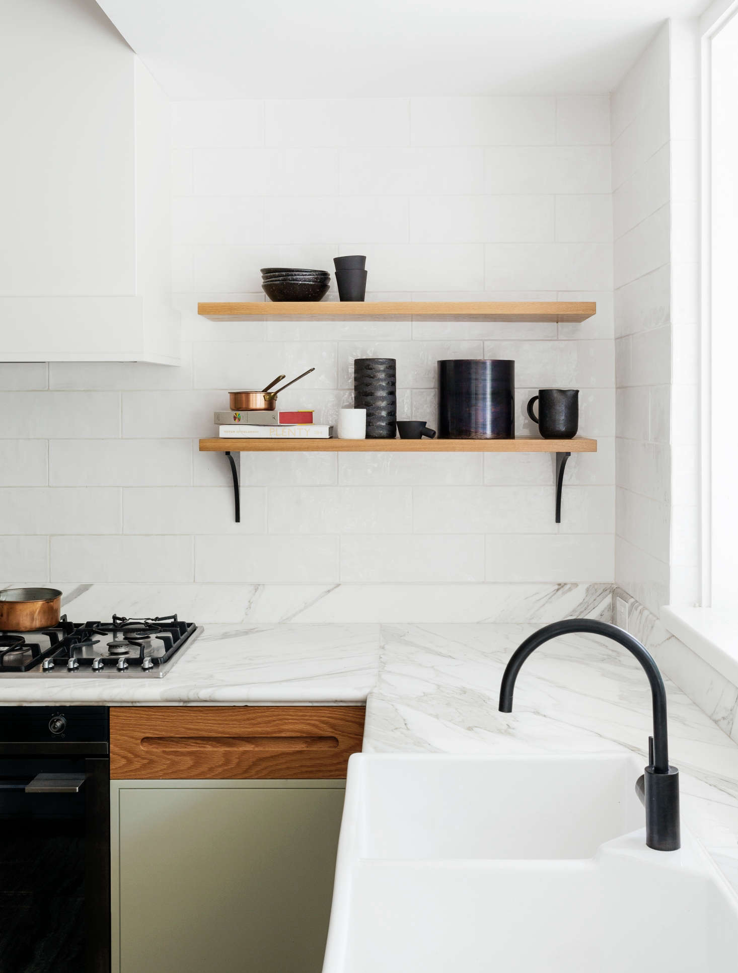 A clean and fresh-looking kitchen remodel with Calacatta marble counters, handmade subway tiles, a black spout faucet, and butler's sink by interior designers Arent & Pyke of Sydney. The cabinets are painted and feature custom oak panels. The open shelves have custom black brackets made of MDF | Remodelista