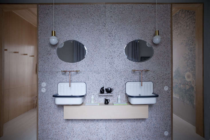 A Room at the Inn 6 Shops with Upstairs Accommodations Alape bucket sinks with copper faucets mounted to a terrazzo wall in the bath.