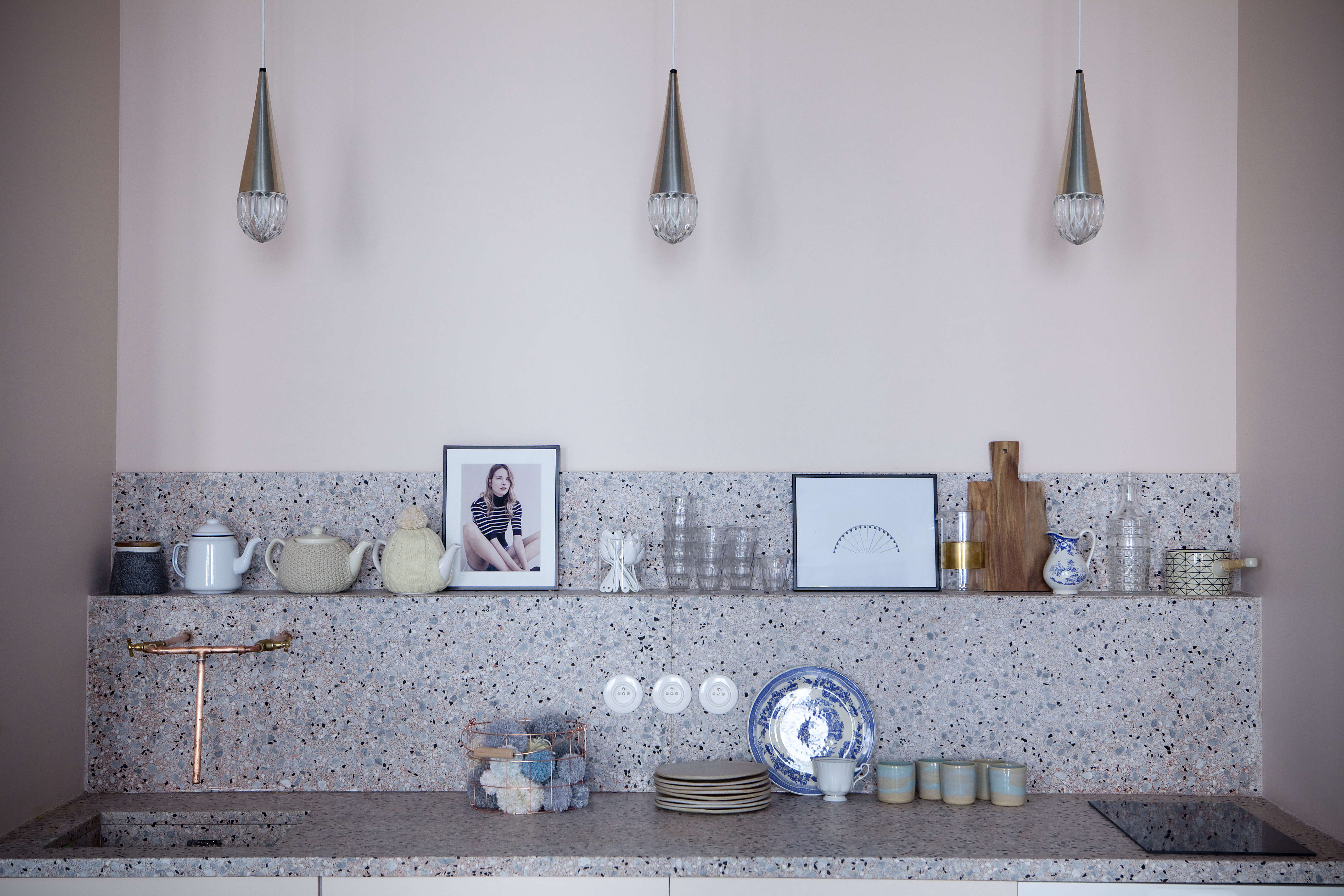 The compact kitchen with terrazzo counters and vintage pendant lights at Chez Marie Sixtine, a guest apartment in Paris, Julie Ansiau photo | Remodelista