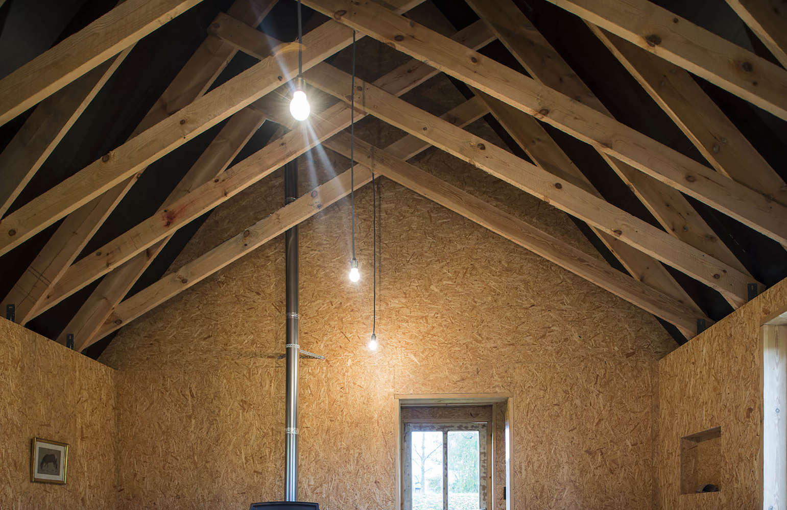 scissor trusses in a cabin in belgium designed and built by london architecture 17
