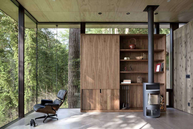 A Puget Sound Cabin That Rests Lightly on the Landscape The living roomis anchored in the forest but features an expansive water view.The ceilings are clad in finished plywood panels, and the home is filled with built ins for storage and aMorso woodstove.