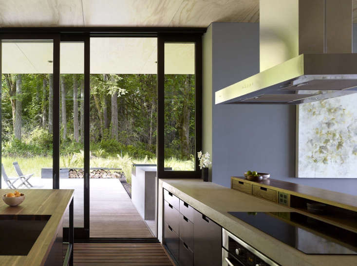 A Puget Sound Cabin That Rests Lightly on the Landscape The kitchen and its immediately adjacent deck both utilize the same water resistant ipe wood flooring.The kitchen countertop is concrete, the custom drawers are blackened steel, and the kitchen island has a butcher block top made of walnut.