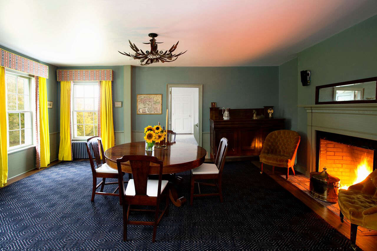 The acid yellow velvet dining room curtains are lined with an ikat print (in the summer, they can be flipped for a lighter look). The light fixture is from a French flea market.