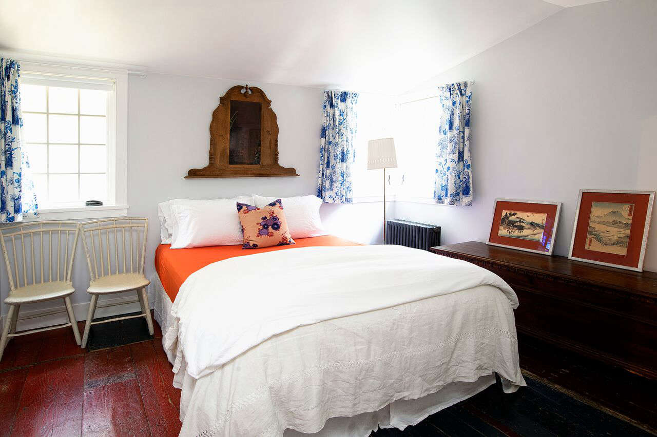 In a guest room, the curtains are made from vintage toile that the owner collected in Paris.
