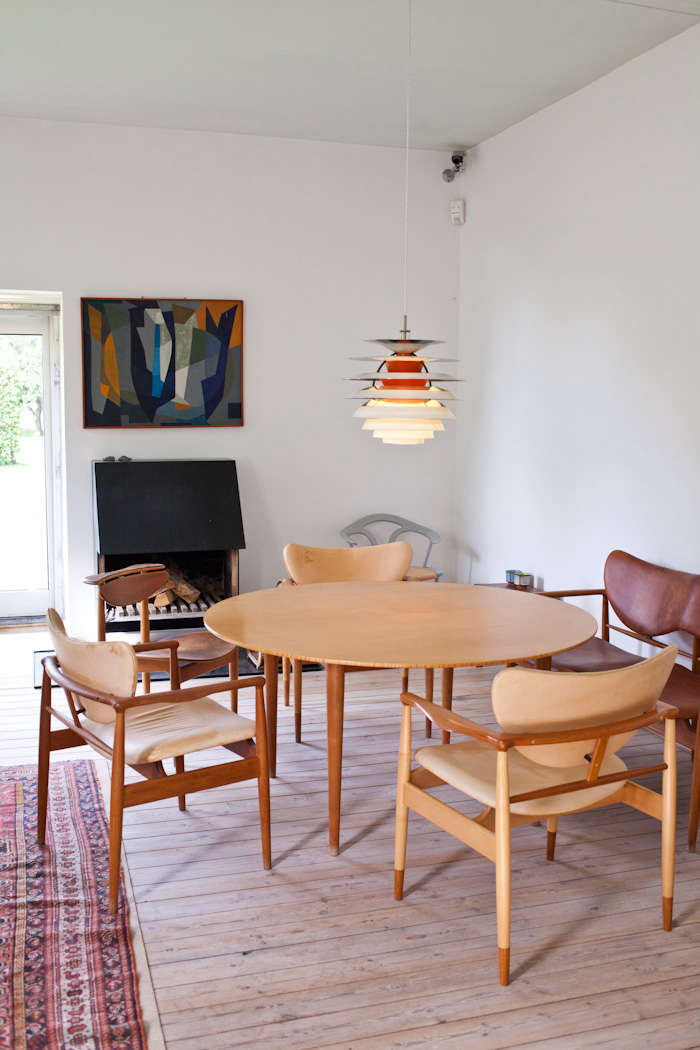 A painting by Jean Deyrolle sets the tone for the dining room palette of pale FJ48 Armchairs and an orange Poul Henningsen pendant.For a similar ceiling paint color, tryFarrow & Ball&#8