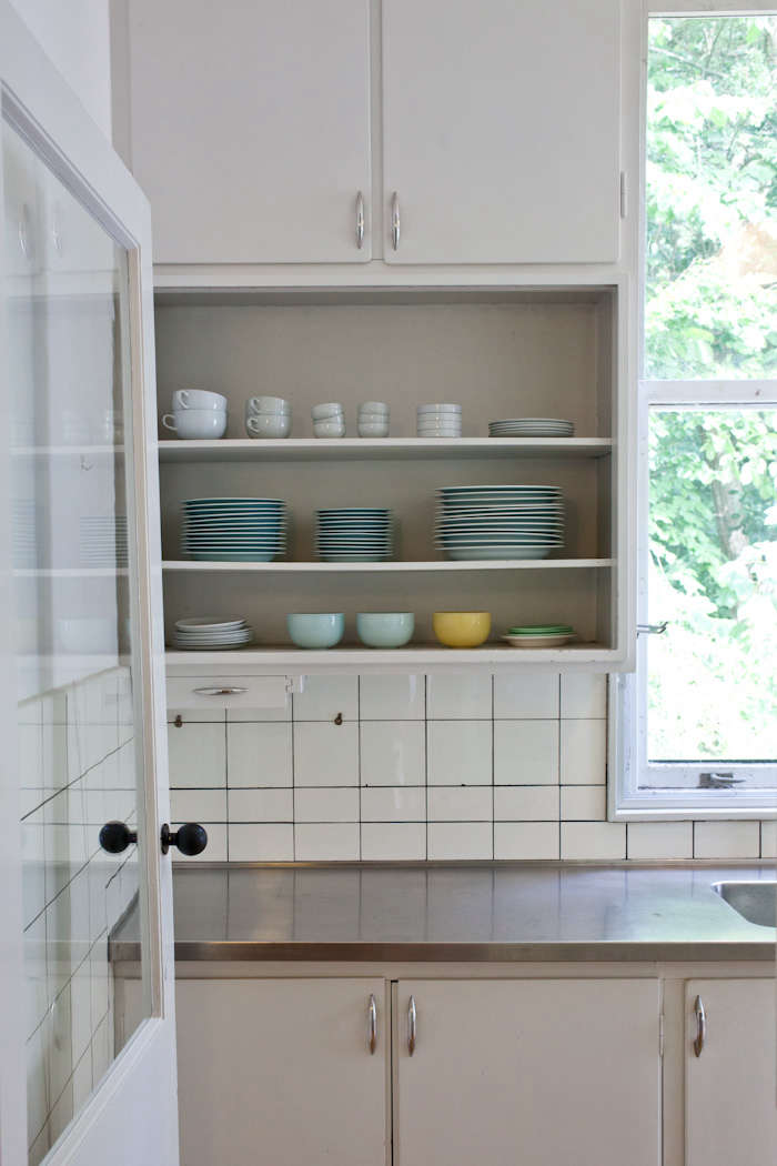 A subdued kitchen of white, gray, and stainless steel is kitted out with blue and yellow tableware.