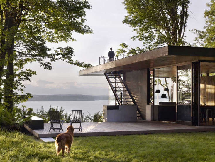 A Puget Sound Cabin That Rests Lightly on the Landscape Though locatedin a rainyclimate, the house is resolutelyindoor/outdoor. Shown here, the kitchen blends directly into an ipe deck with built in grilling station. The architectsdesigned large overhangs at the kitchen deckso the occupants can cook outdoors even in damp weather.