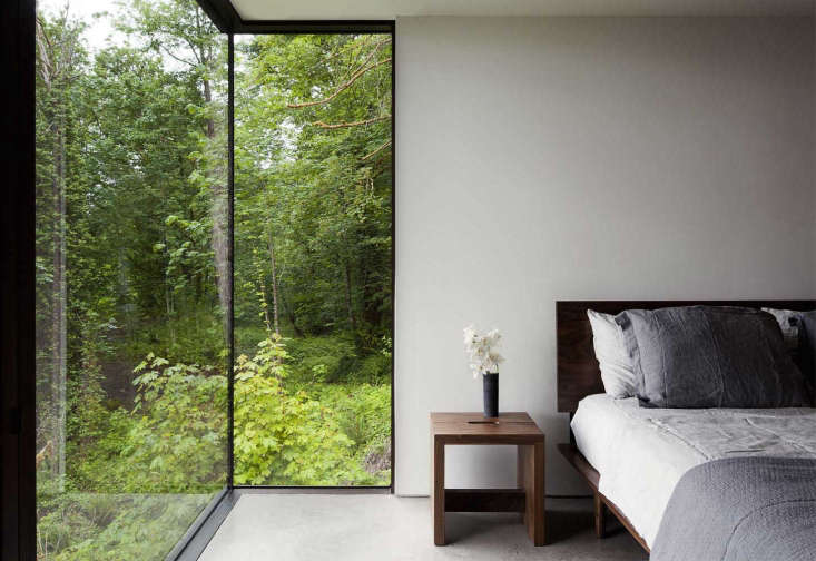 A Puget Sound Cabin That Rests Lightly on the Landscape The master bedroom, the only bedroom on the main level, overlooksthe surrounding forest.The property sits on \20 acres, so the owners did not feel the need for window treatments.