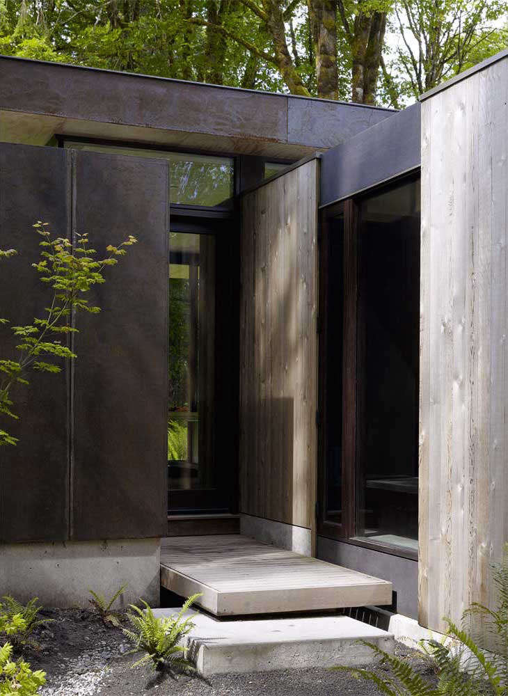 A Puget Sound Cabin That Rests Lightly on the Landscape Though the sliding glass doors between the kitchen and deck serve as an informal entrance to the house, the official entry has a small cantilevered deck welcoming guests into the mudroom.