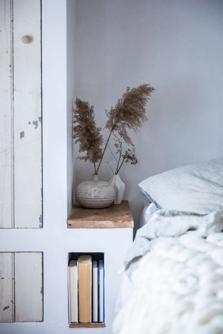 A bedside nook in a weathered remodel by Jersey Ice Cream Co. features charmingly chipped paint. Painting over wax will result in similar contrasting patches. See Old Soul: A Revolution-Era Hudson Valley Home Gets an Update from Jersey Ice Cream Co. Photograph by Beth Kirby of Local Milk.
