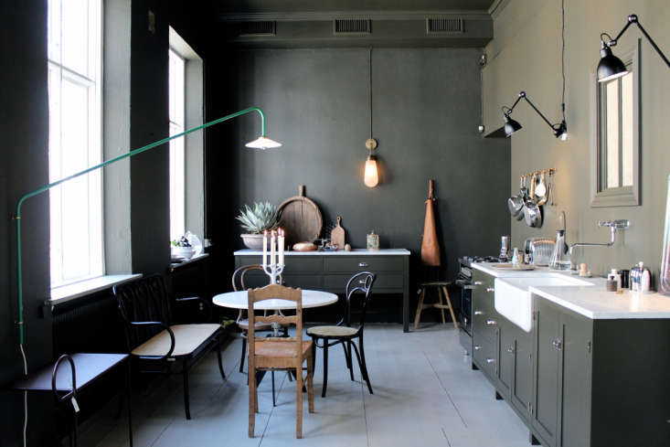 Gothenburg design shop Artilleriet created a shoppable apartmentwith kitchen featuring mismatched dining chairs, army green cabinets, and a pair of Lampe Gras wall-mounted lights. See more in Master Mix: A Shoppable Apartment in Gothenburg, Sweden. Photograph by Johanna Bradford courtesy of Artilleriet.