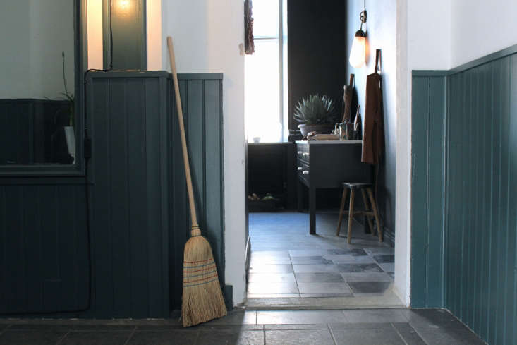 A chair rail (with beadboard wainscoting) is painted a dark green in Master Mix: A Shoppable Apartment in Gothenburg, Sweden.