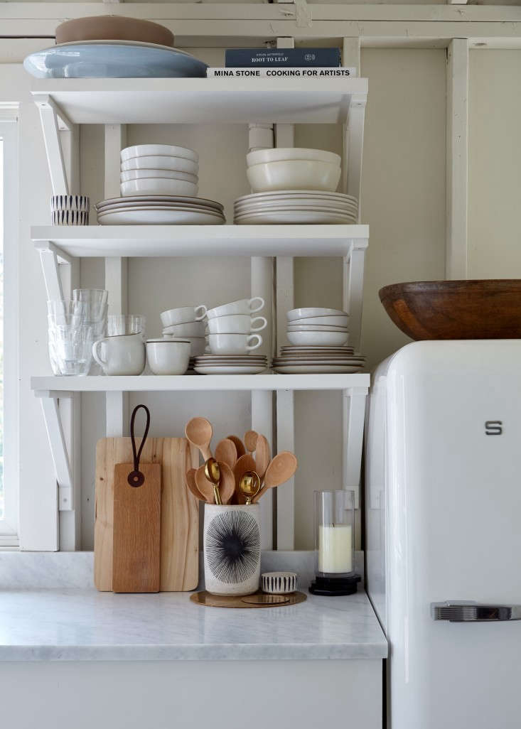First tip for mastering the art of casual tidiness: Mix inexpensive storage solutions with more high-end items. Case in point, Ikea shelves and brackets in a tiny kitchen are suspended just above a handmade ceramic vase (holding wooden spoons) by Michelle Quan. See Bookmark for Next Summer: 7 Storage Ideas to Steal from a High/Low Beach Shack for details. Photograph by Kate Sears.