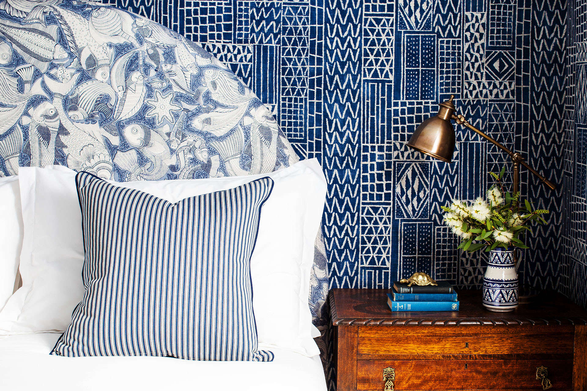 A mix of blue-and-white textile patterns on headboard and walls at Halcyon House, a boutique hotel in Cabarita Beach, Australia, designed by Anna Spiro | Remodelista