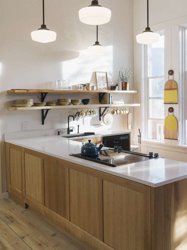 The kitchen is anchored by custom oak cabinets by Phloem Studio, topped with quartz countertops. On the back wall are two Hand-Painted Yellow Cutting Boards by M. Crow & Co., suspended from oxidized cherry hanging pucks with leather cord.